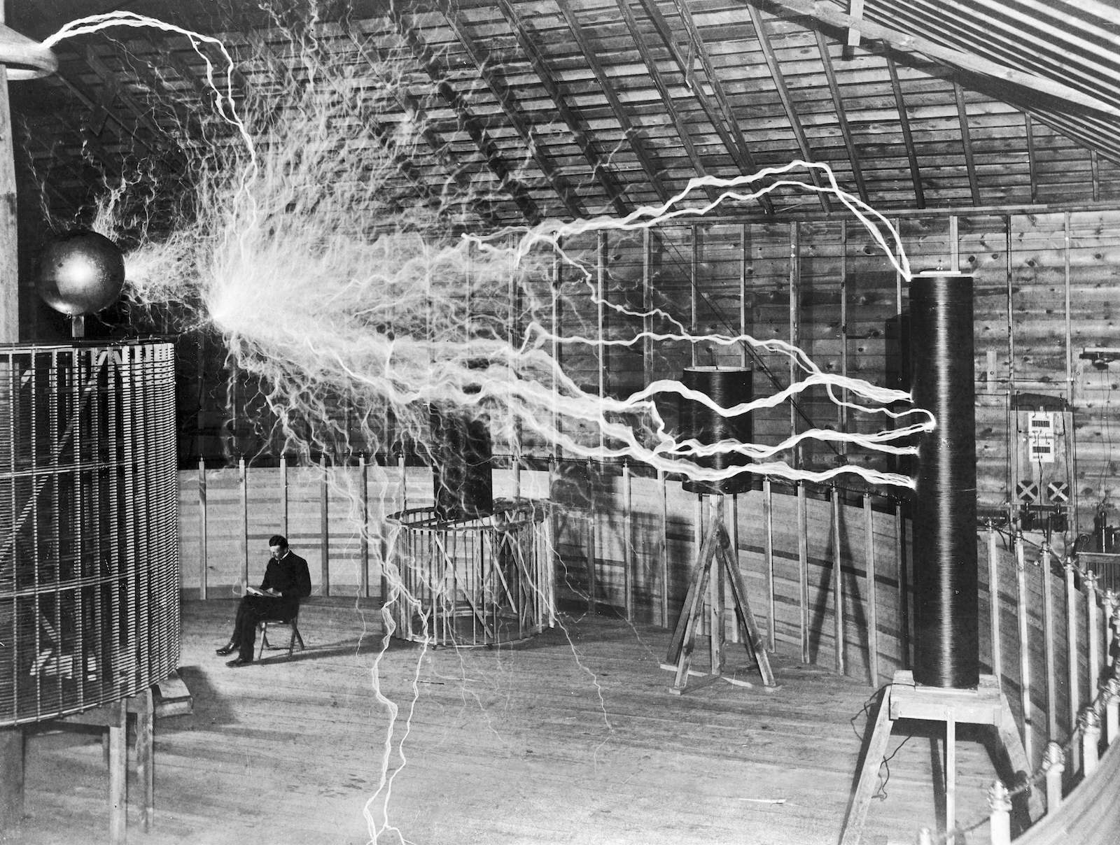 Black and white photo of seated man surrounded by lightening