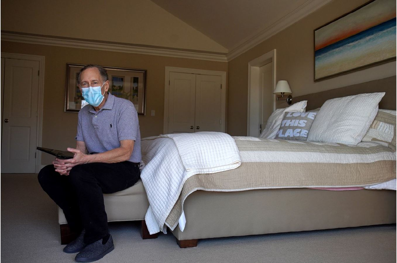 Robert Langer working on a bed at home while wearing a mask