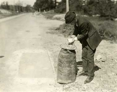 An Unidentified Man Handles Calcium Chloride Flakes on Seven-Mile Road, 2 June 1922