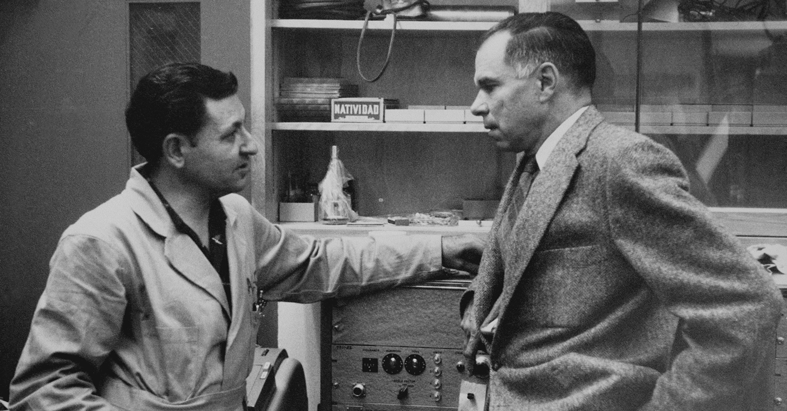 Black and white photo of two men talking in a lab