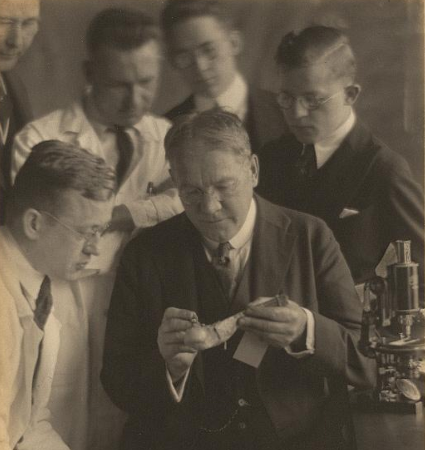 Photo of a group of men with a microscope