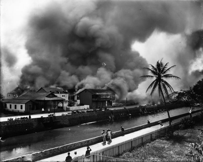 Aerial photograph of buildings on fire across a canal