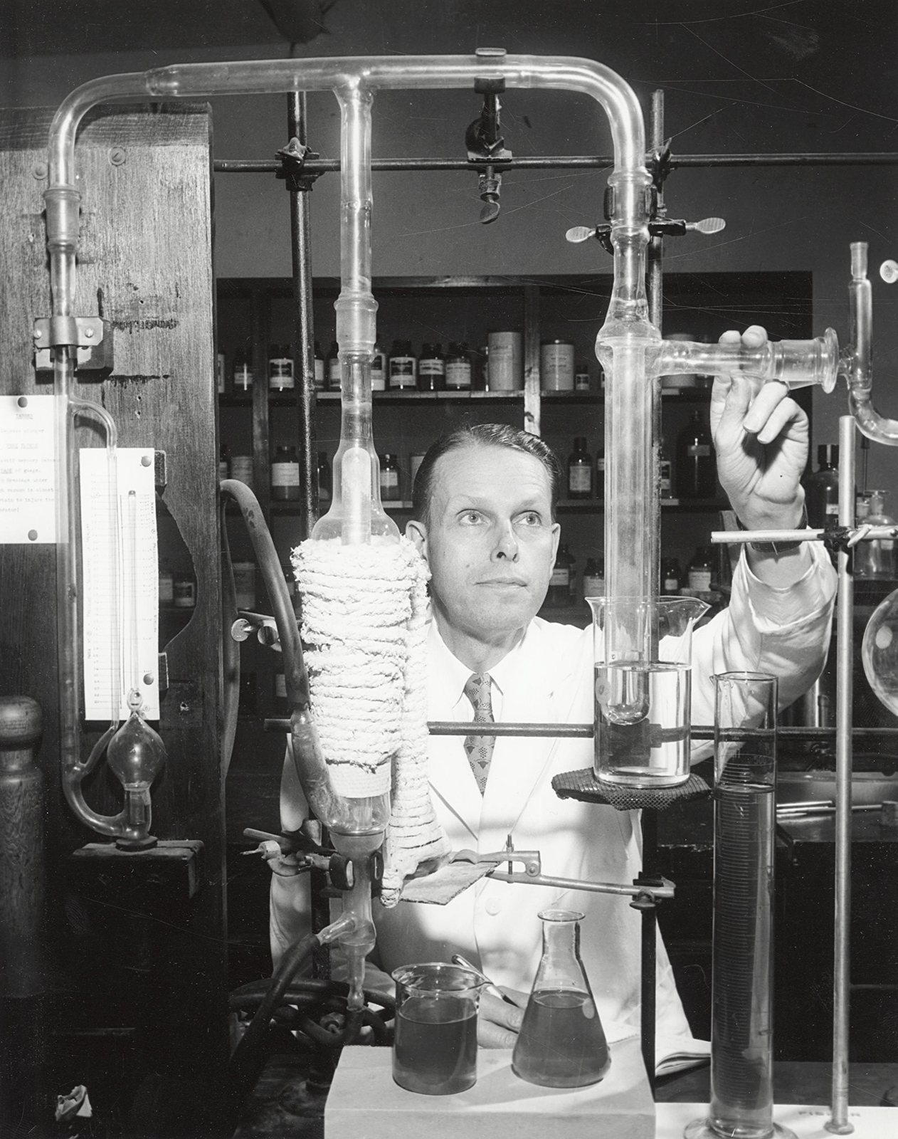 black and white photo of man with glass tubing