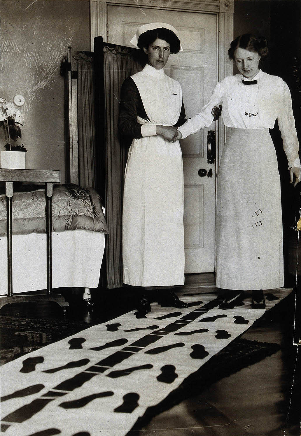 A nurse steadies a patient during physical therapy, undated.
