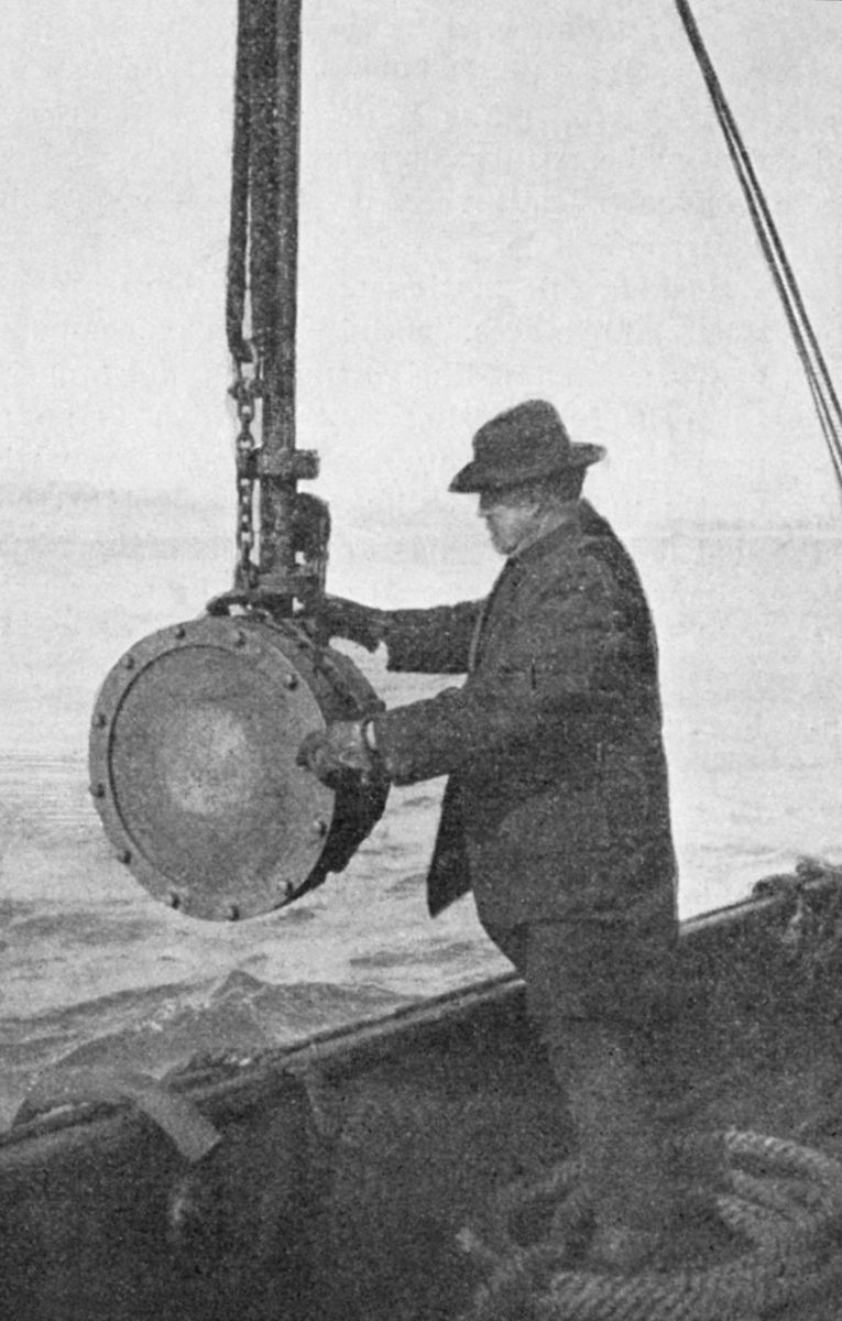 black and white photo of man with equipment on a rope