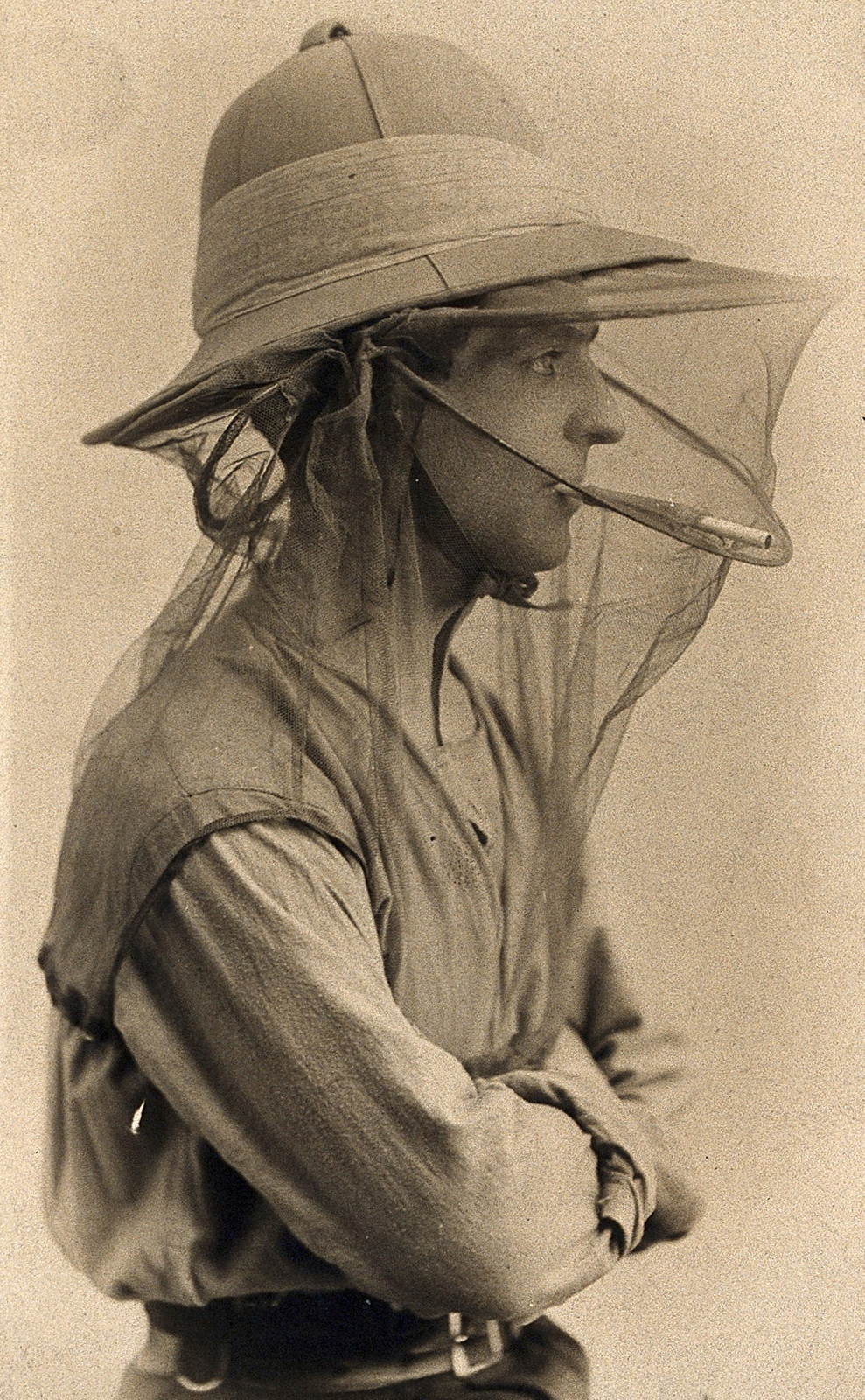Black and white photo of man in pith helmet with net