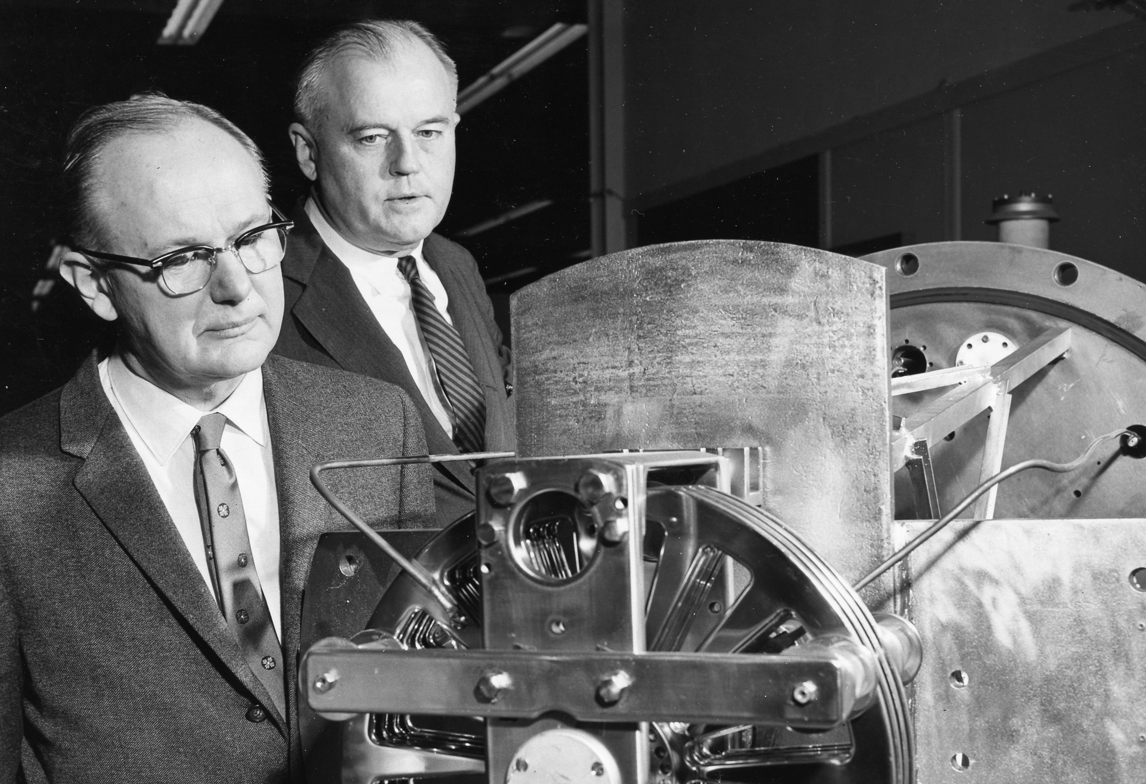 Black and white photo of two men looking at a machine