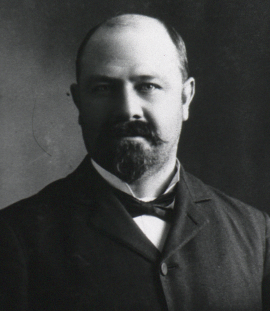 Black and white portrait of bald, bearded middle age white man