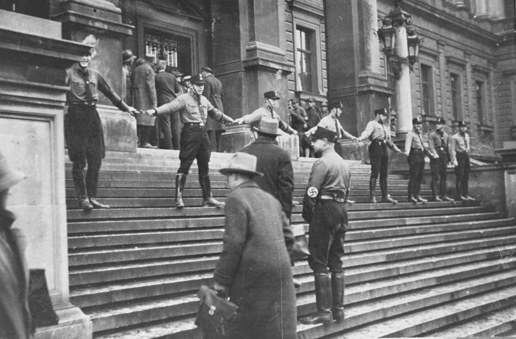 Uniformed men standing on building steps with arms interlocked