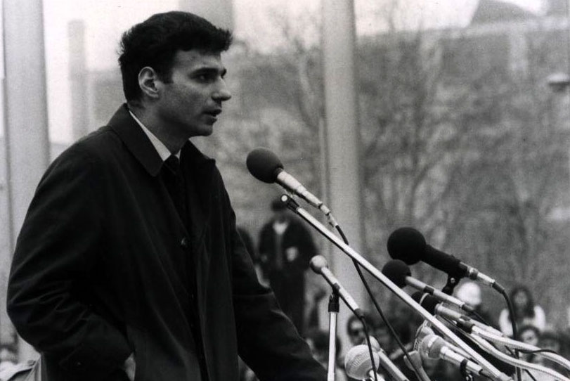 Man speaking in front of microphones outside