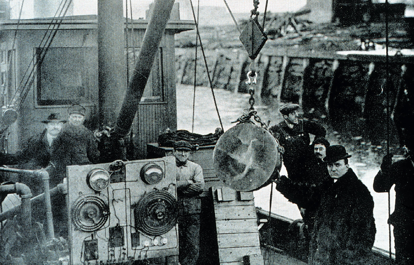 Black and white photo of men with equipment on ship