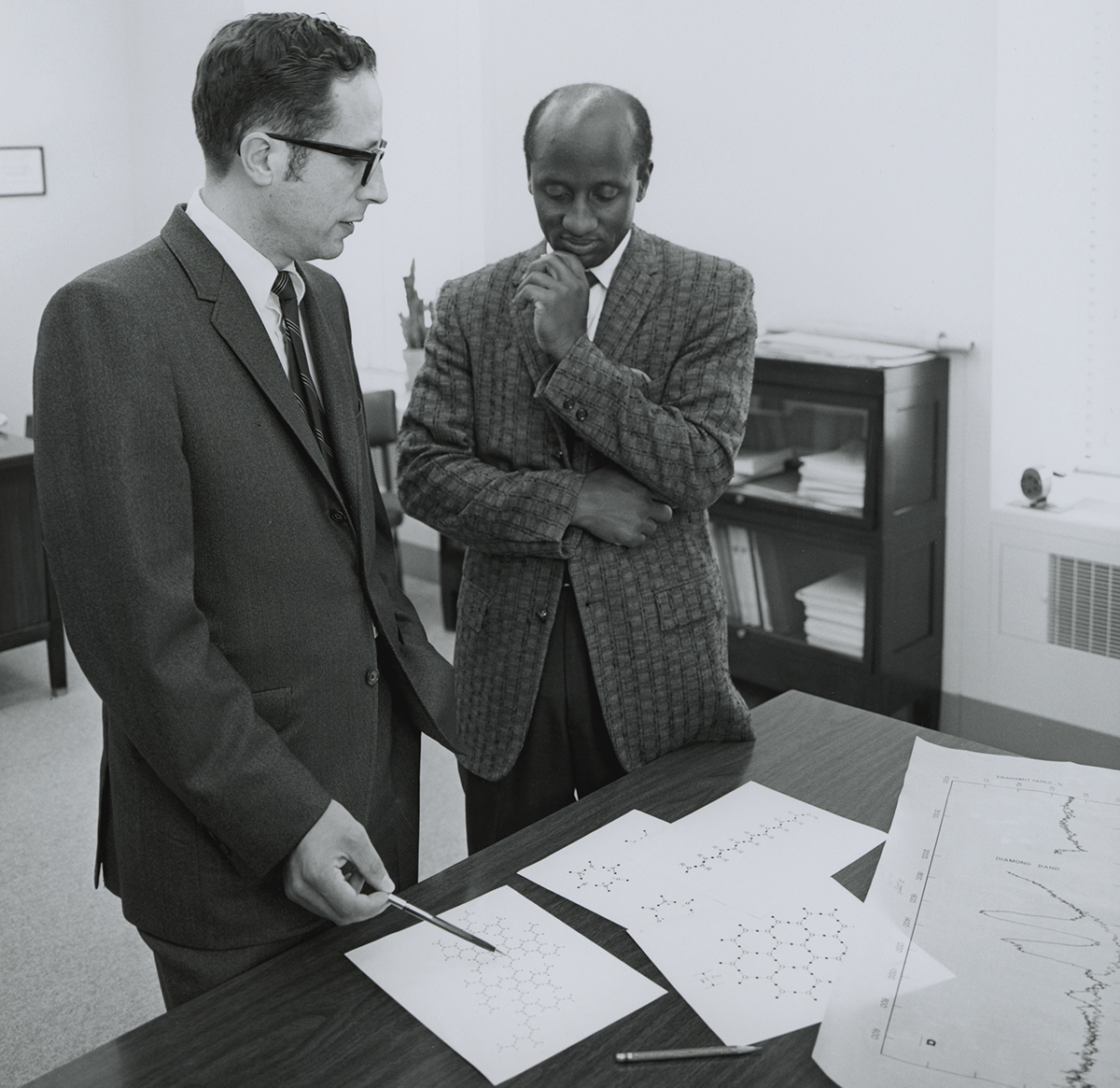Photo of two men standing over a desk