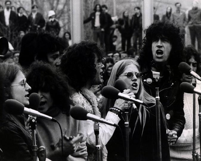 black and white photo of men and women singing