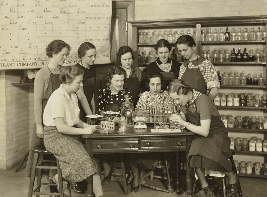group of women standing around a lab table with periodic table in background