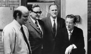 A publicity photo for Waters Associates organic synthesis marketing program taken in Robert Burns Woodward's chromatography lab, 1973. Pictured are (from left to right) Helmut Hamburger, Josef F. K. Huber, James Waters, and Woodward, in front of the ALC-1