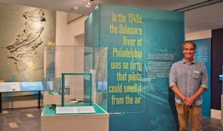 Research curator Jesse Smith shows off Downstream exhibition