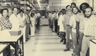 Group of Beckman Instruments scientists standing in a lab and smiling at the camera