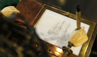 Photo of automaton hand drawing a picture on paper