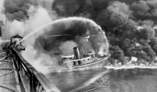 Fire in the Cuyahoga River with a firefighter boat blasting water