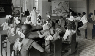 children learning geography in a classroom from 1921.