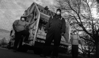 Sanitation workers in masks in front of a garbage truck