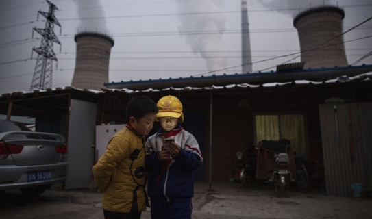 Two children stare at cellphone in front of smokestacks