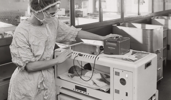 ABeckman model D oxygen analyzer monitoring an infant in an incubator.