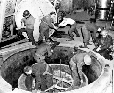 Eight uniformed men working in and around a concrete and steel hole