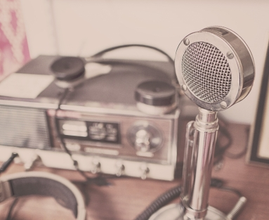 Soft-focus photo of a vintage microphone and headphones