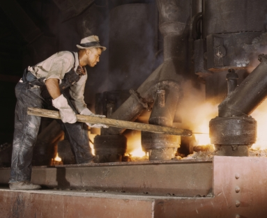 Worker tends an electric phosphate smelting furnace used to make elemental phosphorus in 1942 Muscle Shoals, Alabama.