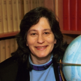 Susan Solomon in her NOAA office in Boulder, Colorado, next to a globe showing Antarctica.