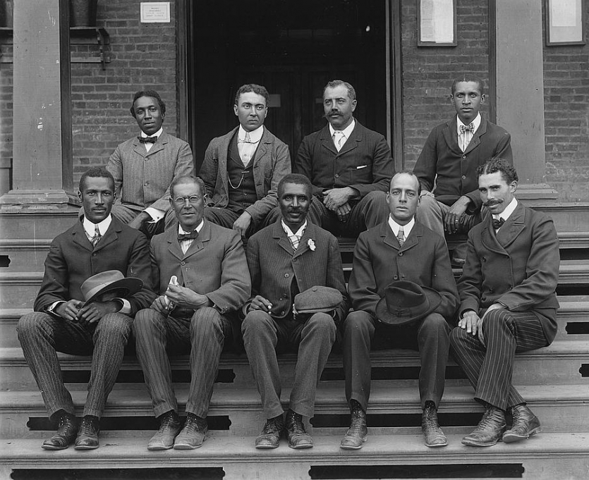 George Washington Carver seated (front row, center) on steps at the Tuskegee Normal and Industrial Institute, with staff, ca. 1902.