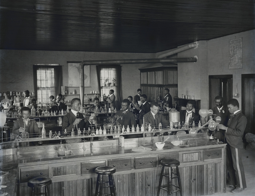 George Washington Carver (second from right) with students in the chemistry laboratory at Tuskegee Institute, ca. 1902.