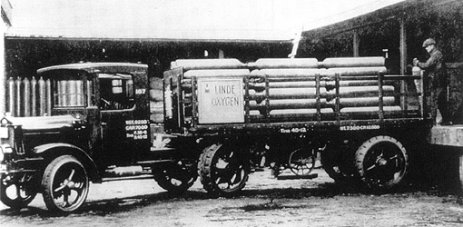 Cylinders of oxygen being loaded on a tractor-trailer truck (1914) owned by the Linde Air Products Company.