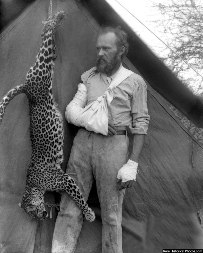 Man with arm in sling with dead leopard
