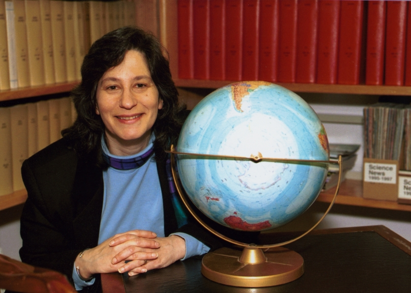 Susan Solomon in her NOAA office in Boulder, Colorado, next to a globe showing Antarctica. Courtesy National Oceanic and Atmospheric Administration.