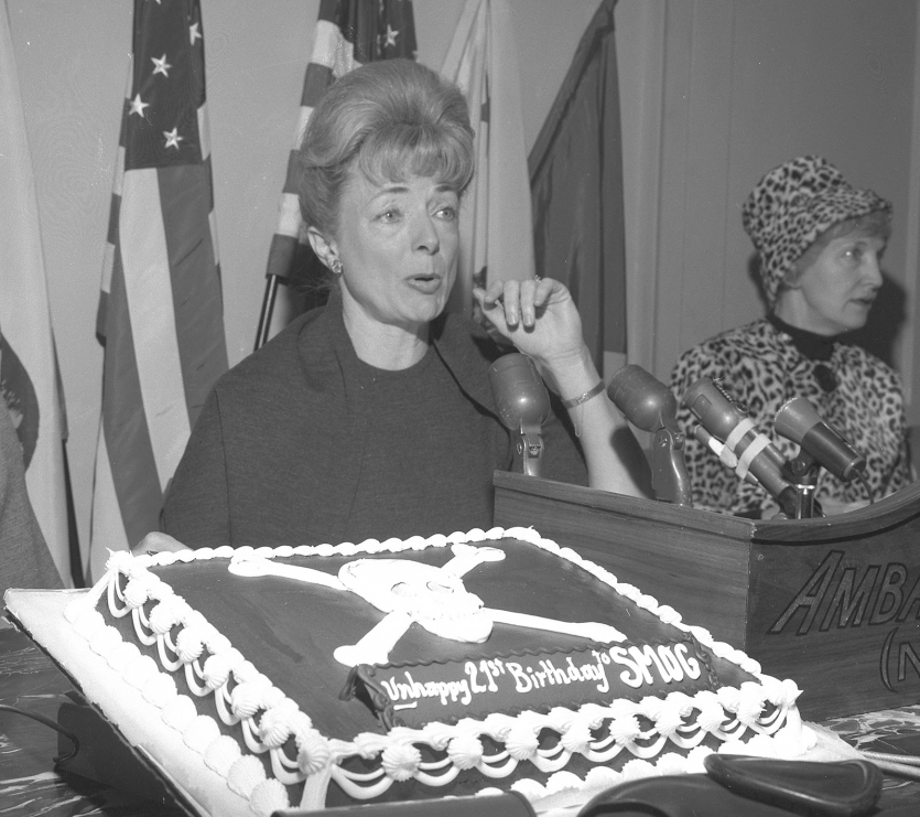 Woman seated in front of microphones with a decorated cake on display