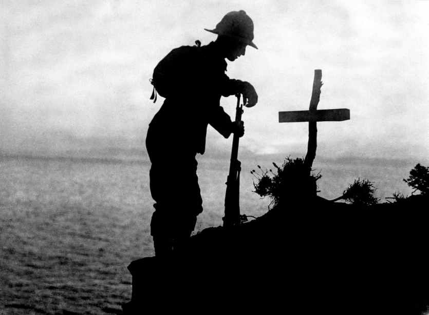 Black and white silhouette photo of soldier and grave marker