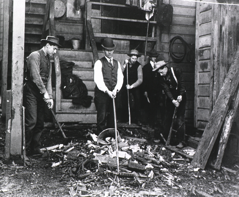Group of men working with rakes and shovels in a cluttered backyard
