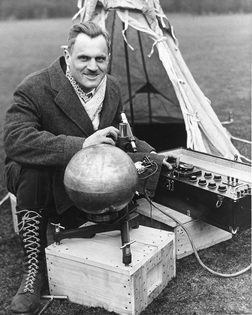 Man in heavy coat outdoors with scientific instruments