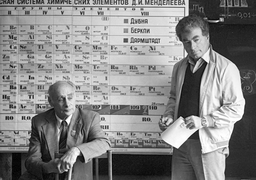Two men (one seated) standing before a periodic table with Cyrillic characters