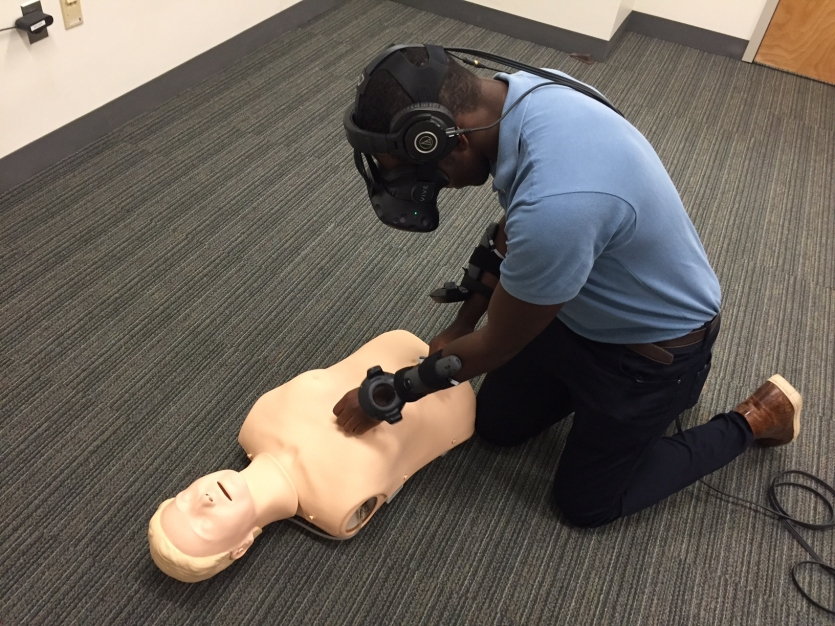 Man performing CPR on dummy using virtual reality headset