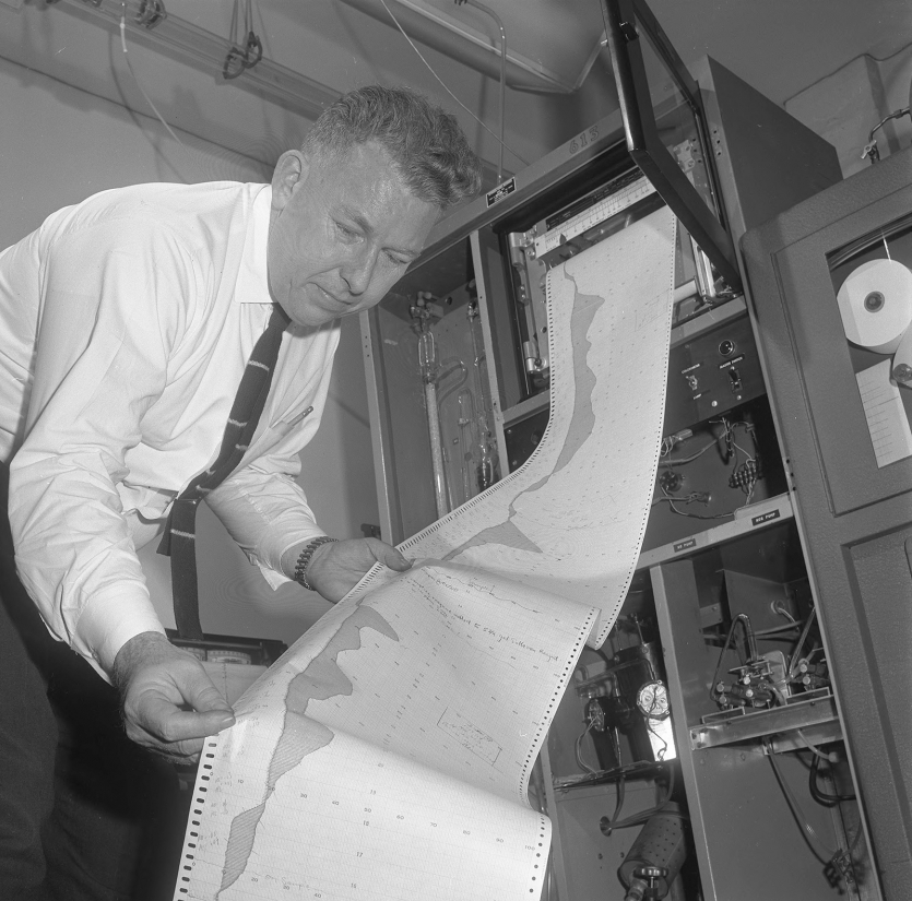 Man holding a long printout of air-monitoring data