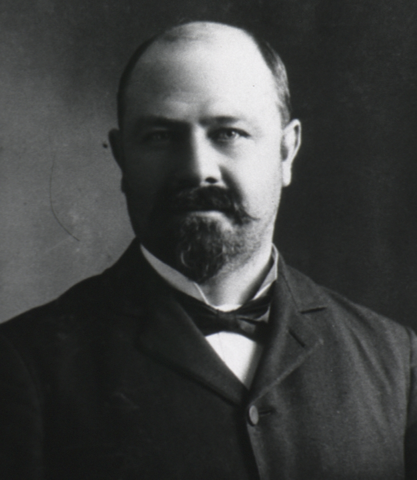 Black and white portrait of bald, bearded, white man