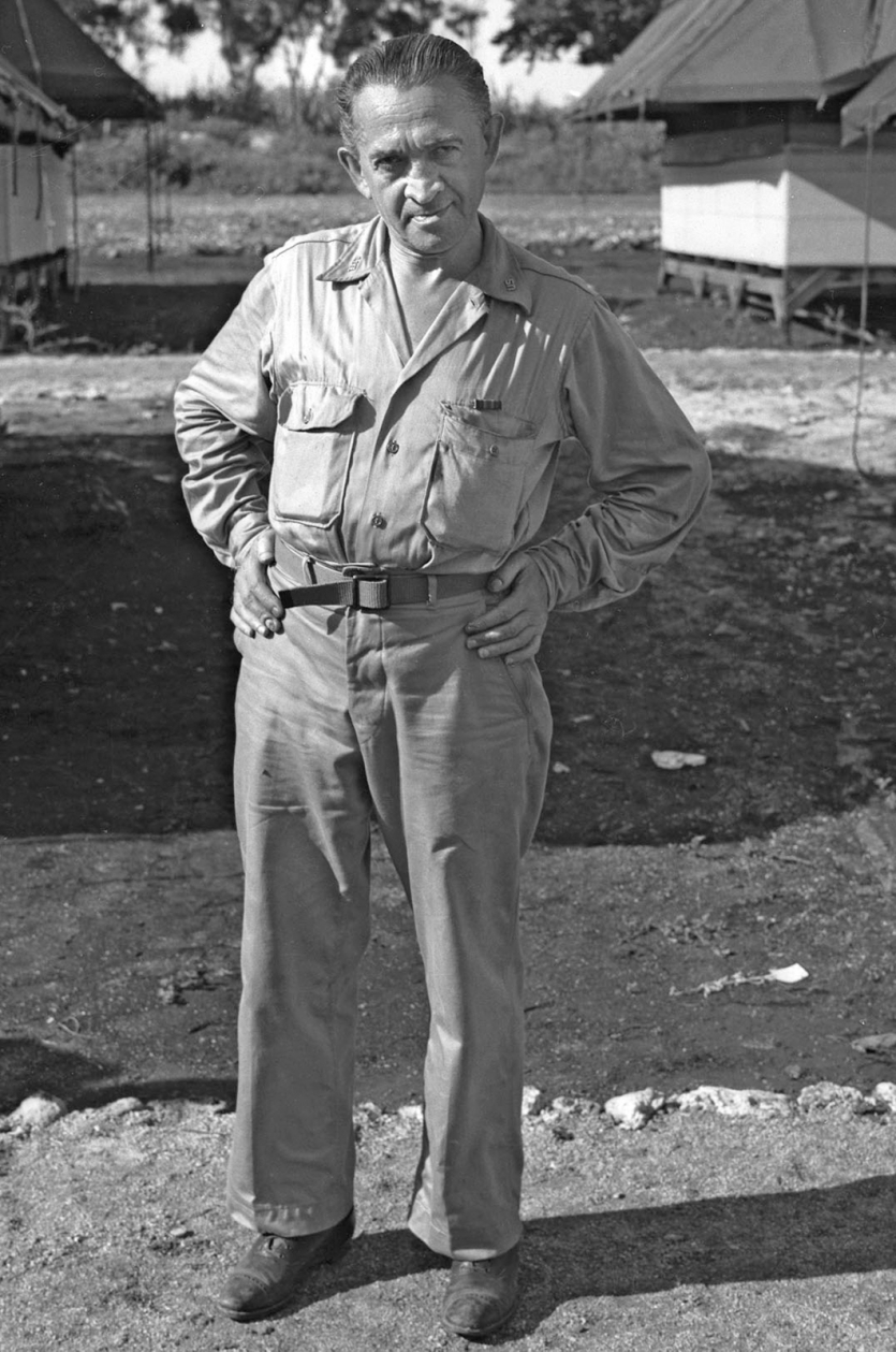 Laurence in military dress standing in temporary camp