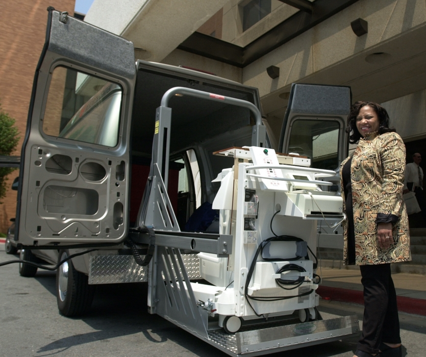 Woman standing with medical instrument outside van