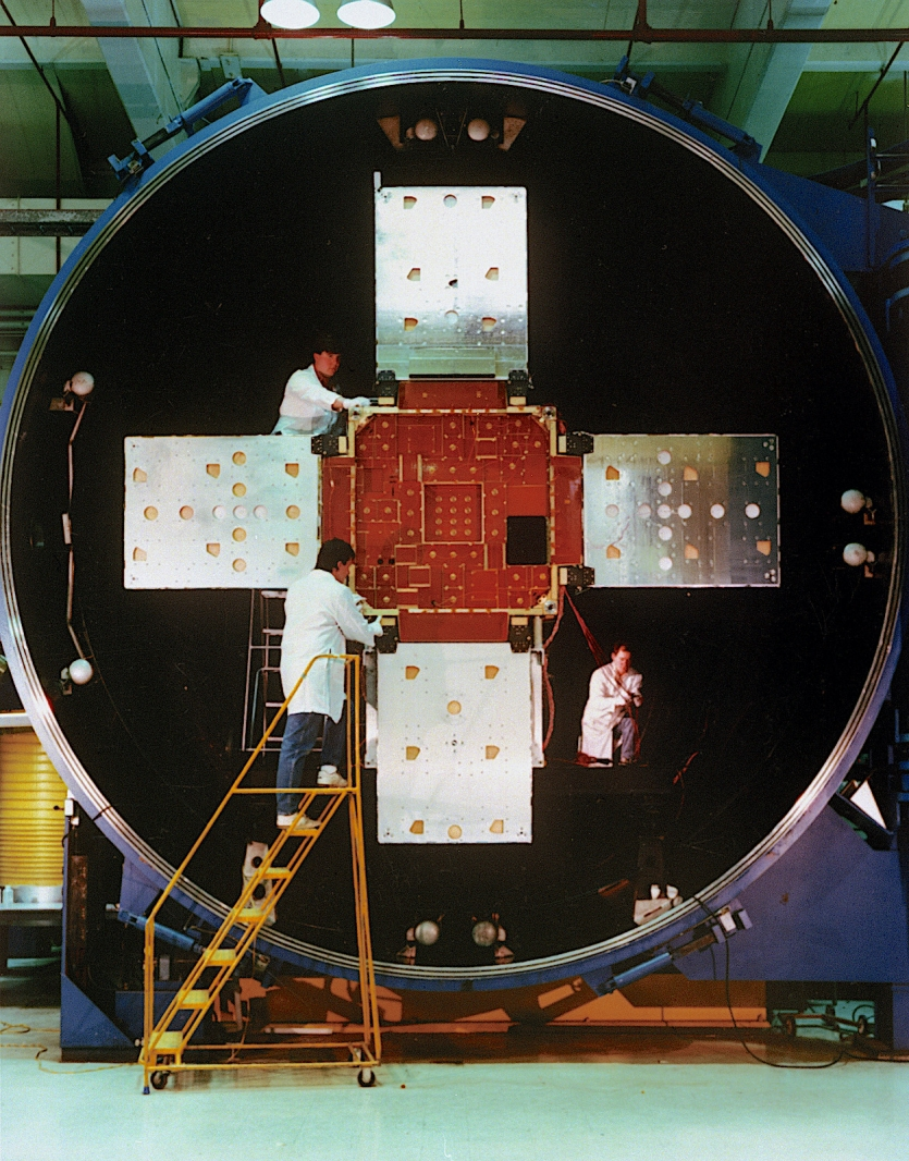 Three people in lab coats working on a satellite