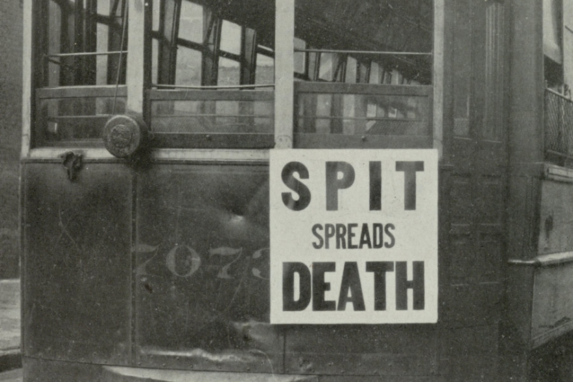 "Streetcar with sign reading ""spit spreads death"" in 1918"