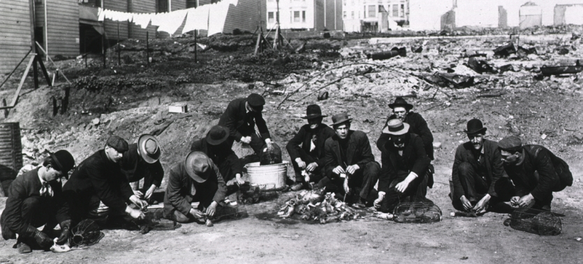 A group of twelve workers crouching and tying tags on dead rats